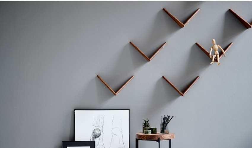 Dark brown Cadovius butterfly shelves against a grey-washed wall, as wall decorations to spruce up the home.