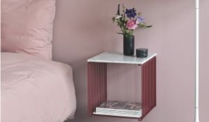 Copper red panton wire cube, covered by marble, against a light pink wall, serving as a bedside companion.