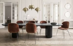A regal atmosphere brought about by the placement of GUBI's Beetle Dining chairs, round a Moon Dining table. Accompanying them are pure, white walls, gold multi-lite pendant lamps and gold-rimmed Randaccio Circular mirrors.