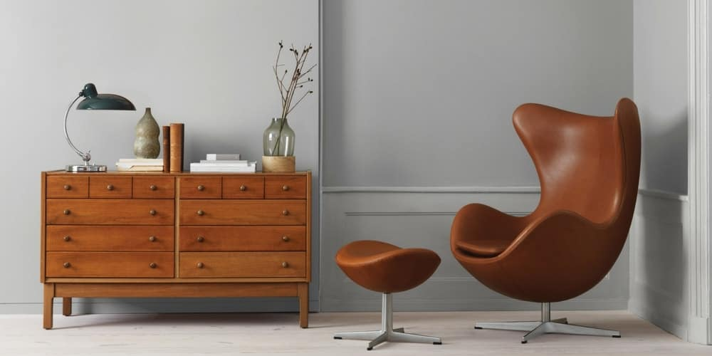 Brown egg chair by Fritz Hansen against a grey backdrop