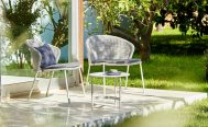 A Pair of Lean Outdoor Lounge Chair in White Grey Cane-Line Weave, in an outdoor setting