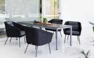 Cane-line Mega Outdoor Dining Chair in Dark Grey with Light Grey Cushions around a grey table - Danish Design Co Singapore