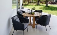Cane-line Mega Outdoor Dining Chair in Dark Grey with Light Grey Cushions around a teak table - Danish Design Co Singapore