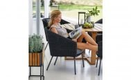 Cane-line Mega Outdoor Dining Chair in Dark Grey with Light Grey Cushions with a lady reading - Danish Design Co Singapore