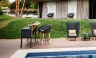 Cane-line Peacock Outdoor Bar Chair in dark grey with a light cushion by pool - Danish Design Co Singapore