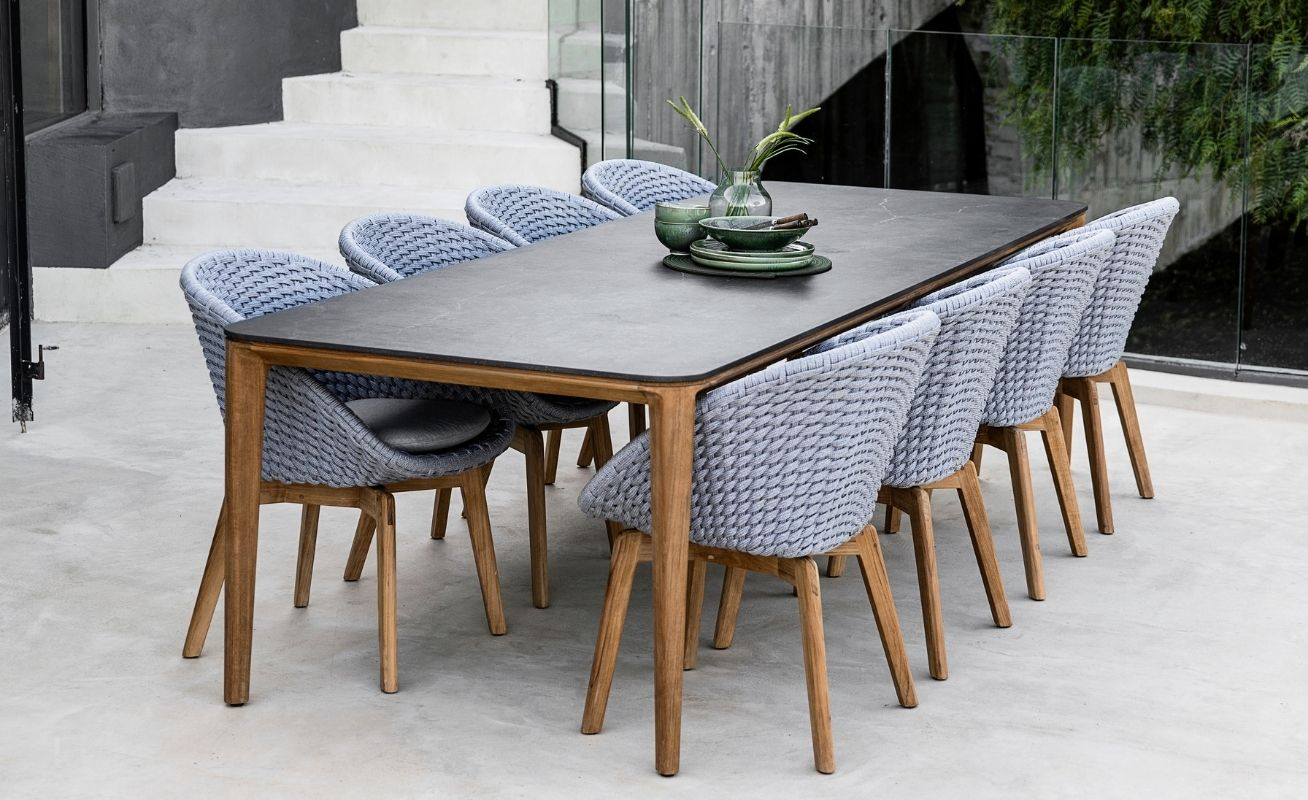 Cane-line Peacock Outdoor Dining Chair Light grey seat with light grey cushion and teak legs on patio - Danish Design Co Singapore
